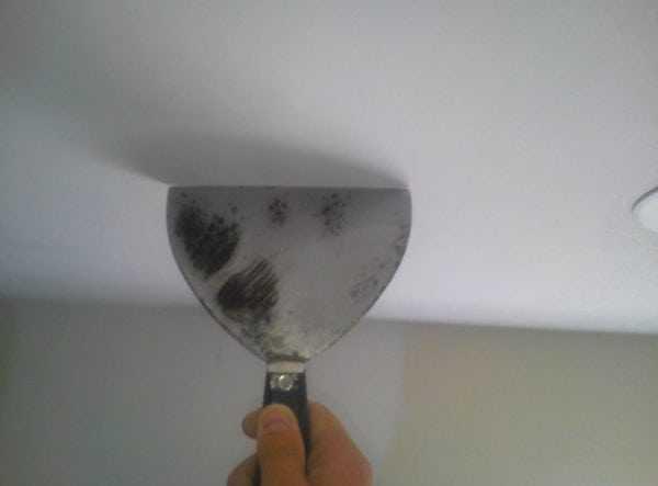 Использование шпателя для очистки потолка
