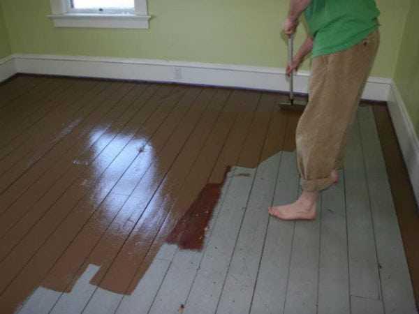 Женщина красит деревянный пол
