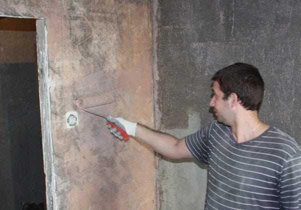 Мужчина наносит бетоноконтакт на стену