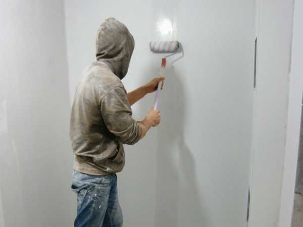 Мужчина грунтует стены