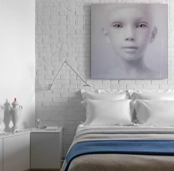 Одна стена в спальной комнате стилизована под кирпичную кладку