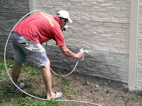 Мужчина красит забор белой краской