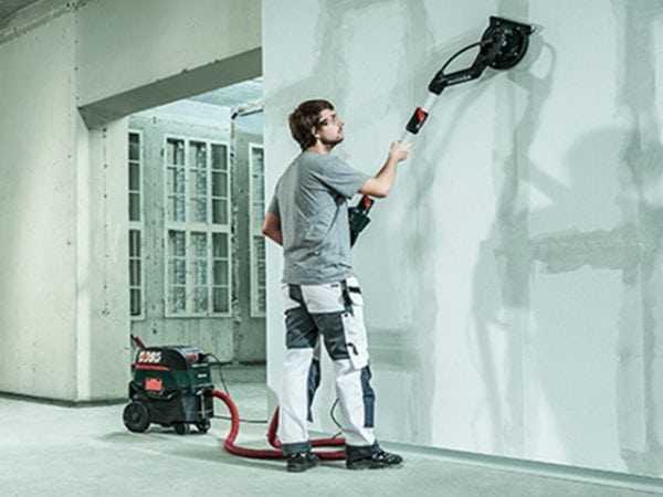 Обработка стен после шпаклевки шлифовальной машиной