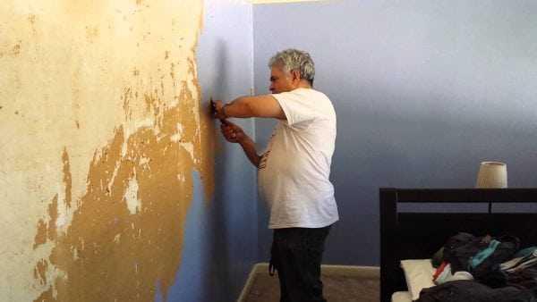 Отслаивающиеся участки краски нужно снять со стены