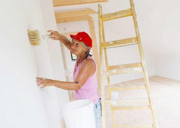 Женщина грунтует стену