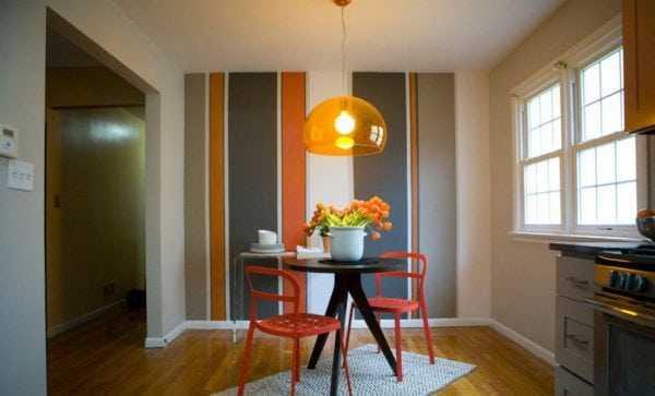 В комнате стена покрашена в полоску под общий вид