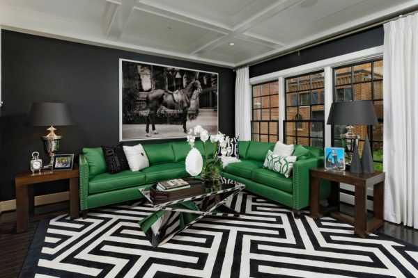 Зеленый диван на фоне черных стен